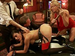 Sexy slave-waitresses are naked and bring all kinds of toys which are used on them by horny masters and mistresses. Alani gets her mouth gagged and Beretta her pussy fucked with a big dildo. It is very interesting that her pussy was already wet, which means she is really slutty and likes being treated as one!