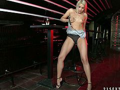 Blonde bombshell Brandy Smile is having some fun in a bar. She strips, demonstrates her awesome body and fingers her snatch before drilling it with a dildo.