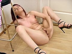 Lovely redhead chick on high heels takes her black dress off and lies down on the floor. She spreads her legs and fingers herself.