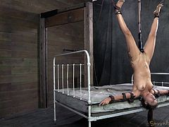 Jynx Maze is tied up and hung from the ceiling by her slave master Matt Williams. She has a gigantic dildo shoved into her cunt and clamps attached to her nipples. She's tied to the edge of the bed and gets her mouth fucked hard.