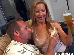 Arousing and seductive tanned blonde milf with big natural knockers and bouncing ass gets naked and enjoys giving head to her experienced neighbor in living room while her hubby is at work