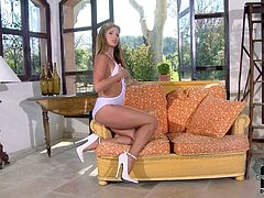Glamour babe Eva Parcker in white swim suit takes off her shoes and shows off her bare feet and lovely legs as she poses on the sofa. Watch lovely girl in white have some fun alone.