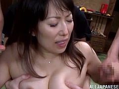 Lewd Japanese milf is playing dirty games with a few guys indoors. She sucks their cocks reluctantly and then gets her vag fucked hard doggy style.