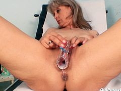 Frisky tasty looking granny pisses into the bowl during the gynecologist appointment. Later she climbs on the gynecological chair in order to gets her oversized pussy examined using speculum.