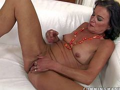Turned on old black haired whore with natural tits and cheep make up gets naked and enjoys stuffing her cunt with gigantic rubber dildo on white couch in solo fantasy