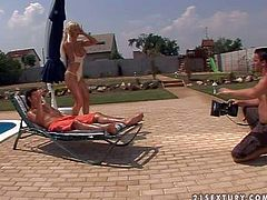 Attractive young blonde stunner Krystal with big firm hooters in white swimsuit and stripper shoes teases tall stud with muscled body and gets his stiff pecker up her ass by the pool