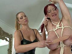 Topless curvy redhead Vanessa with enormously big tits gets seriously punished by blond-haired domina Carol in the living room. Watch her get her massive melons spanked painfully.