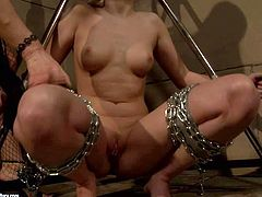 Young looking nude blonde in chains gets set in very uncomfortable position and tortured by experienced long haired cougar with tight ass and big tits in tight black dress