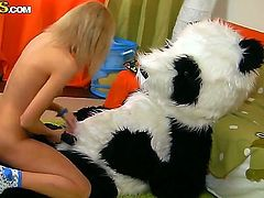 Skinny blonde teen Sveta with natural boobs and pretty face takes off hot pants and plays with gigantic black dildo while riding on her full size panda doll in kinky fantasy.