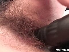 Redhead slutty mature shoving large dildo up in her hairy cunt