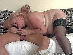 Pale fake mature blonde blonde whore with hanging tits and long nails in stockings and high heels seduces young buck with muscled body and enjoys sucking his cock long time