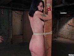 Kinky bitch gets tied up to a wooden post. Her Master spanks her ass and then turns a jet of water on her vagina. After that he puts her in the water.