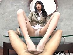Hot Japanese girl in office clothes sits on a glass coffee table. She gives great footjob to some lucky guy in point of view video.