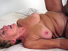 kinky old bitch lies down on a bed and gets fucked deep in her hairy withered pussy by much younger guy.