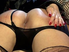 Spoiled brunette milf lies on the kneels of rapacious domina with mouth tied in ripped pantyhose while getting her tight asshole finger fucked and later poked with a dildo.