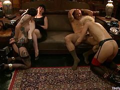 Hot babes in stockings and garters get humiliated. Later on they suck big dick and get fucked hard on a sofa. They also get their tits pinched.