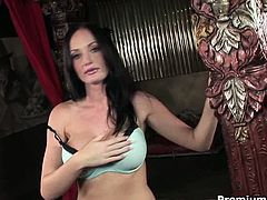 Frisky brunette porn star with big enhanced tits takes off her lingerie to demonstrate her cuddly body before she starts pounding her shaved snatch with dildo.