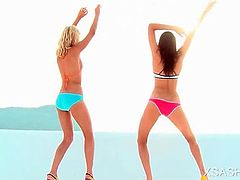 Sasha and her brunette girlfriend sensually stripping swim suits at the beach