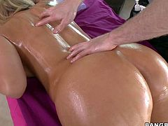 Stunning blonde milf Nikki Sexx with big firm hooters and huge jaw dropping ass gets naked and covered with oil while young handsome stud is massaging her hole curvy body