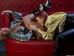 Insatiable red-haired domina teases a ruined shaved cunts of fuckable blond milf with a vibrator while poking her asshole with anal beads in arousing lesbian sex video by Tainster.