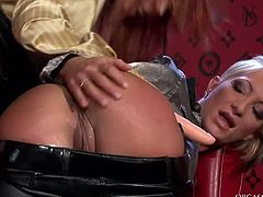 Alluring blond milf stands in doggy pose exposing her shaved pinkish asshole for a rimjob before a spoiled red-haired domina starts drilling it with a dildo.