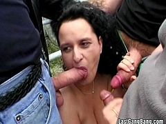 Watch this outdoors gangbang scene where a slutty brunette mature sucks big cocks outdoors until her mouth's filled by cum.