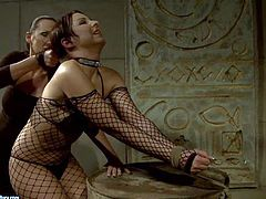 Gorgeous dark haired slave girl in fishnet body stocking gets chained and dominated by her mistress in a basement and enjoys in showing her big sexy ass to her