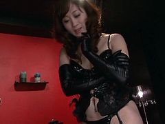 Sexy Japanese milf wearing latex clothes and stockings is having fun with some dude indoors. She rubs her feet against his dick and moans sweetly in pleasure.