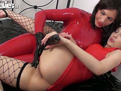 Provocative bitches are wearing red color latex dresses with fishnet stockings. Tanya pokes Sarah's pussy with fat dildo. The latter moans and quivers with pleasure.