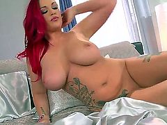 Yummy chick with big boobs and long red hair is lying on the bed alone in black heel shoes and passionately pleasing herself with masturbation.