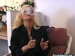 Hot blonde with big natural tits likes to smoke when posing her nude body