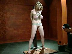 Blonde chick with big ass and boobs lies on the floor with her legs opened being tied up. She gets hit with electricity and then toyed with a strap-on.