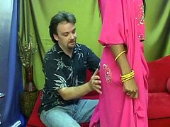 Ugly Indian slut in exotic costume seduces a perverse white tourist. She sits with legs spread aside as he enjoys tongue fucking her shaved vagina in sultry sex video by Indian Sex Lounge.