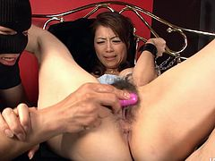 Sizzling Japanese milf gets her hands tied to the bed while a kinky dude teases her small perky tits and bearded vagina with mini vibrators before he pokes it with a dildo.