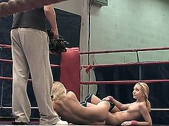 Pretty young slender blonde hotties Nataly Von and Nikky Thorne with tight asses and natural boobies get naked during arousing chick fight in the ring while referee films them.