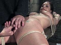 A big titty brunette whore gets tied up and put into a big-ass fish tank with water while she's got rope on her titties and pussy.