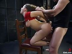 There's a kinky girl in red latex outfit going through some hot bondage action that also sees her pussy getting fucked hard.