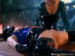 This cruel mistress in latex outfit is in the disciplinary mood. She plays with her slave's pussy and pounds it with a black sex toy.