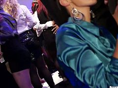 Playful brunette chics kneels down in front of kinky dudes during corporate party celebration to mouth fuck their hard cocks in sultry group sex video by Tainster.