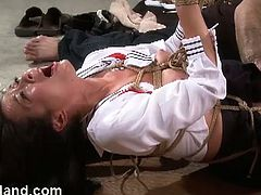 Nyssa is a brunette slave bounded to wooden pillars. Her master is toying her pussy with a vibrator and some beads.