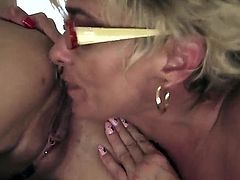 Dark haired slender babe Betty Stylle with long legs and pierced belly button gets her shaved minge and tight firm ass licked good by short haired mature blonde Jessye.