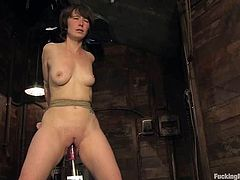 Short-haired chick gets tied up in some wooden barn. After that she sucks big dildo and gets her pussy toyed by the fucking machine.