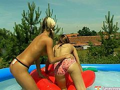 It's hot summer day. Two slim brunette and blond teens with small natural tits are in the pool. They get bored just swimming. So spoiled long legged gals get rid of bikinis to play with tits and rub each other's clits right in the water.