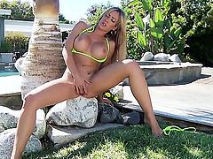 Naughty blonde doll Capri Cavalli with nice firm hooters and delicious tight ass in green bikini gets naked and polishes sweet cunny in backyard on a hot summer day.