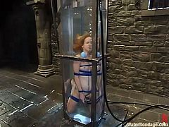 This girl fancies herself the next Houdini because she is locked up with her arms and legs bound. She is thrown into a tall water tank filled with cold water and she tries to escape. The tank is filled to the top as she struggles to get free.