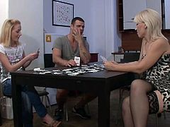 They're playing strip poker and after a number of hands he takes off and lets him mom and girlfriend continue on. Once he's gone and the game is over, mom uses a dildo and fucks his girlfriend's pussy.