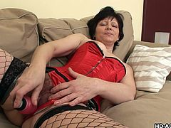 This sexy mature woman with black hair is masturbating on her couch in her sexy fishnets. Her husband walks into the room and helps her. He rubs her boobs and she sucks on his rock hard cock. She loves the taste of his cock.