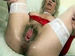 Dirty granny wearing red corset and white nylon stockings exposes her nasty hairy cunt. She gets her clam stuffed with big dildo while sitting on a couch spreading legs wide. Provocative porn video of kinky mature woman presented by 21 Sextury.