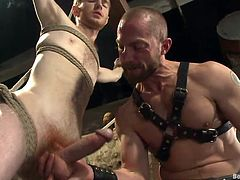 Adam Herst is a muscle bound gay dominatrix who has tied up twink slave Seamus in the sex dungeon. The slave is bound in rope and can't move or fight when his master wraps his lips around his cock and sucks him hard. He fondles his balls and jerks him off.