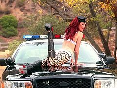 Stunning redhead babe in sexy police uniform makes an amazing show. She lies down on a police car hood and shakes her perfect ass. This babe also shows her pink pussy and small tits.